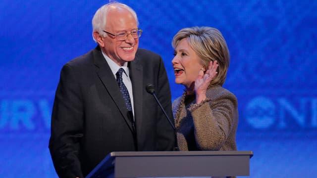 Mann und Frau stehen während TV-Debatte lachend nebeneinander, sie hebt die Hand.