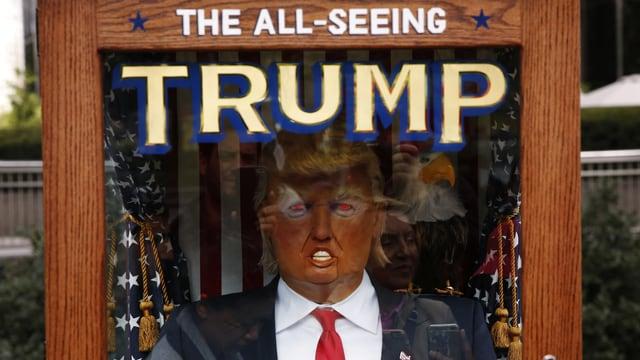 Trump-Puppe hinter Glas in Holzkasten