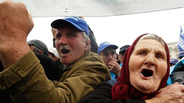 Zwei Rumänen schreien während einer Demonstration, einer von ihnen hält eine Faust in die Höhe.