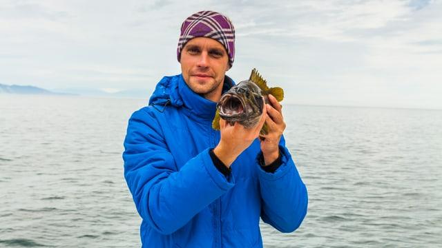Ein Mann hält einen Fisch in die Kamera