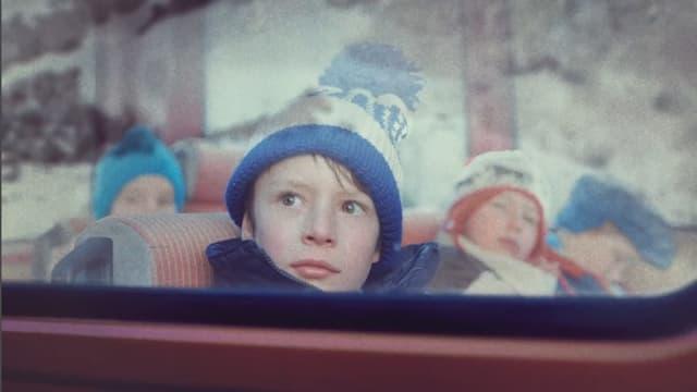 Ein Junge sitzt in einem Bus. In der FEnsterscheibe spiegelt sich ein Berg, an dem ein Bergsturz niedergeht.