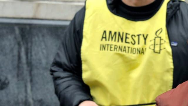 Ina part d'in um. Ins vesa mo ina vesta cun l'inscripziun Amnesty Internationa.