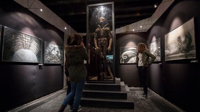 Visitaders che guardan sin ina sculptura da H.R. Giger