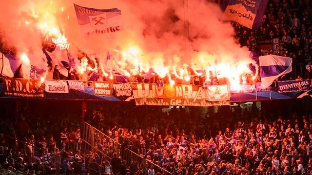 Tribüne im St. Jakob-Park mit feiernden Schalke-Fans, die auch Pyros abbrennen.
