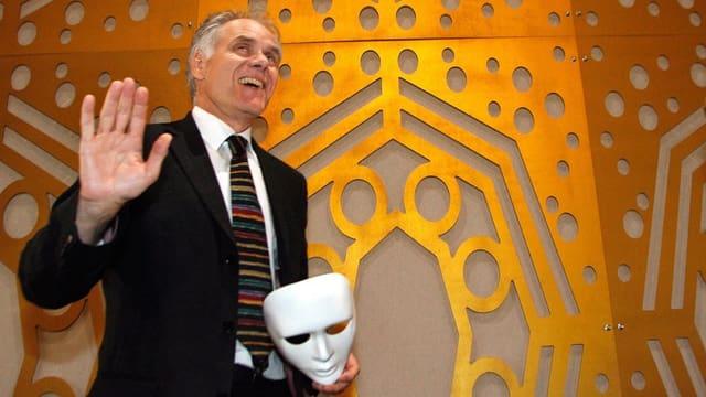 Moritz Leuenberger an der Einweihung des romanisches Theaters im Jahr 2006. Er hält eine Maske in der Hand.