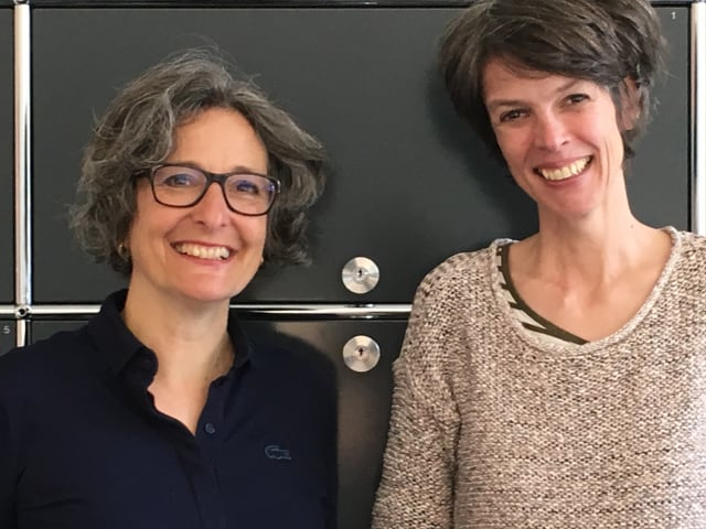 Die beiden Historikerinnen Claudia Engler (links) und Birgit Stalder vor einer Bürowand.