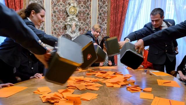 Ratsweibel leeren Urnen auf den Tisch der Stimmenzähler.