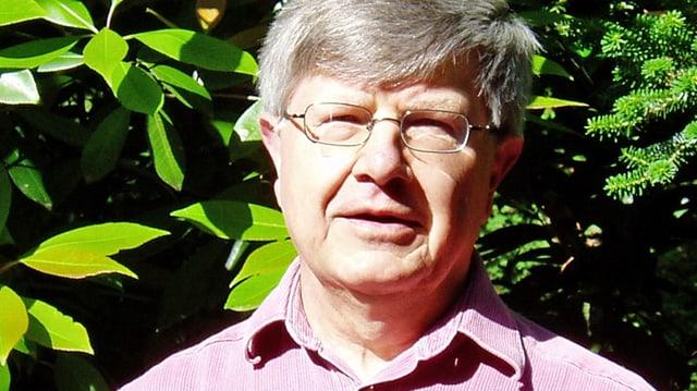 Ein Mann mit Brille und grauen Haaren, im Hintergrund ist ein Gebüsch erkennbar.