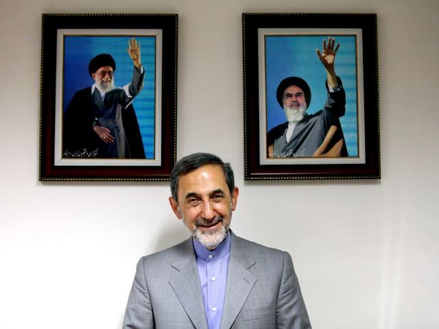 Velayati vor Bildern der Revolutionsführer Chamenei und Chomeini.