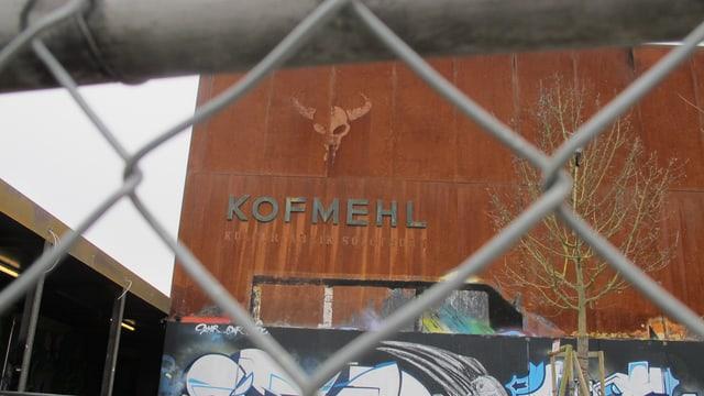 Blick von aussen auf die rostrote Kulturfabrik Kofmehl - im Vordergrund unscharf zu sehen, der Drahtzaun.