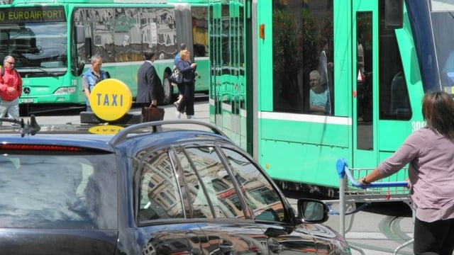 Menschen vor einem Tram und einem Bus der BVB.