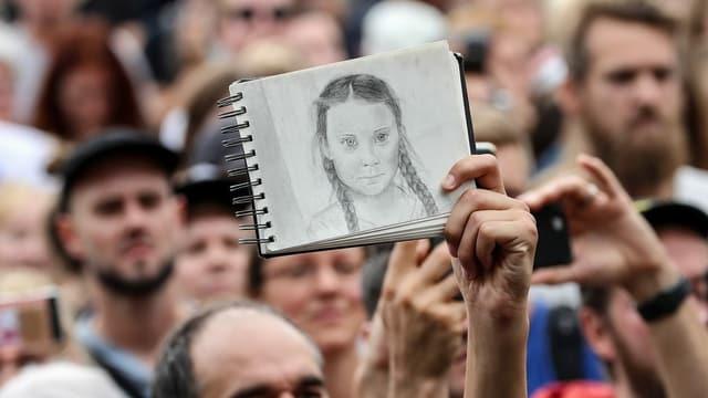 Bei einem Protest hält jemand eine Zeichnung von Greta Thunberg in die Luft.