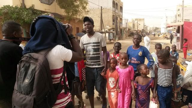 Ein Videodreh mit schwarzen Kinder in einer staubigen Strasse Dakars,