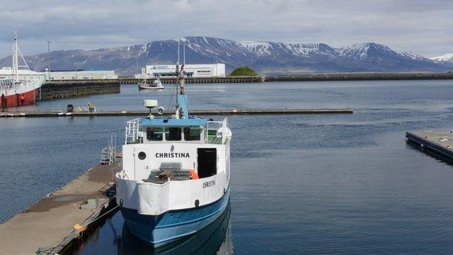 Boot im Hafen von Reykjavik. Im Hintergund Hügellandschaft.