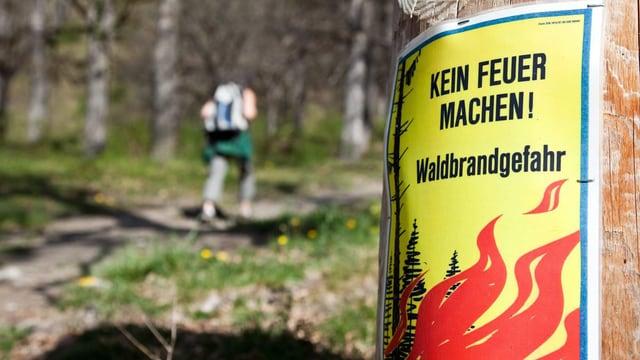 Plakat an einem Baum, das vor der Waldbrandgefahr warnt.