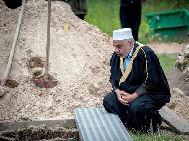 Mann kniet vor einem Grab.