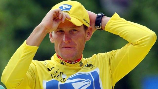 Lance Armstrong hält eine Schirmmütze.