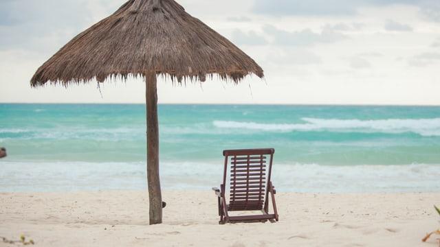 Sonnenschirm und Liegestuhl vor Meereskulisse.