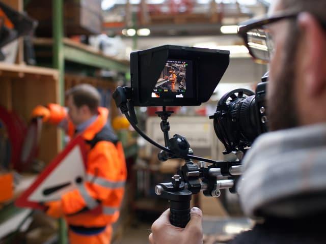 Im Vordergrund sieht man auf den Display einer filmenden Kamera, die Gabriel filmt. Gabriel ist gross aber unscharf im Hintergrund zu sehen, wie er ein Schild aus einem Regal nimmt.