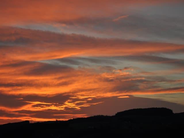 Der Himmel über Konolfingen scheint zu brennen. Die aufgehende Sonne taucht den bewölkten Himmel in Orange und Rot.