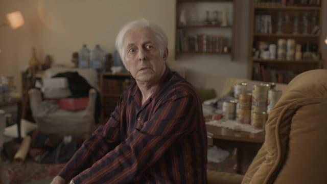 Ein Schauspieler, der Gurlitt spielt, sitzt in Pyjama in einem unaufgeräumten Wohnzimmer.
