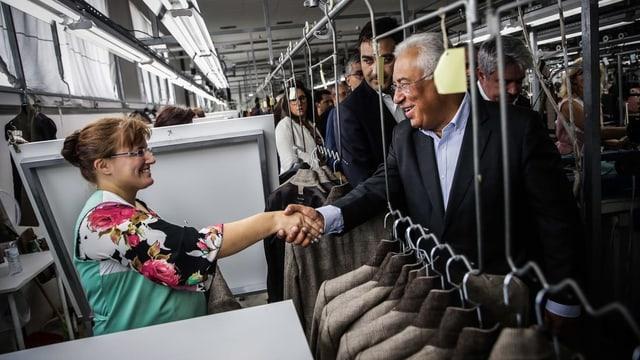 Costa schüttelt die Hand einer Arbeiterin.