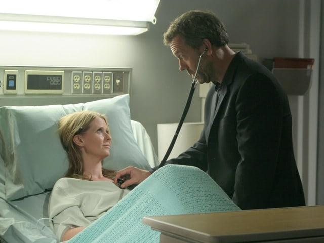 Dr. House untersucht eine Patientin mit dem Stethoskop.