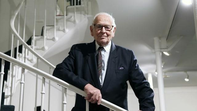 ein alter Mann steht auf einer weissen Treppe