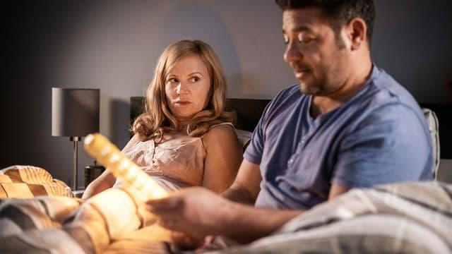 Ein Paar im Bett, der Mann hält einen Dildo in der Hand.
