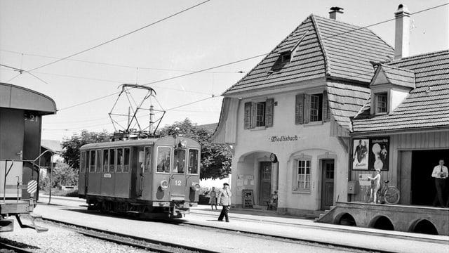 Bahnhofgebäude mit einem Waggon der einem Strassentram ähnlich sieht.