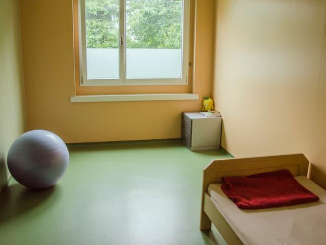 Schlichte Zimmereinrichtung mit Gymnastikball, Bett, Kommode und Plüschtier.