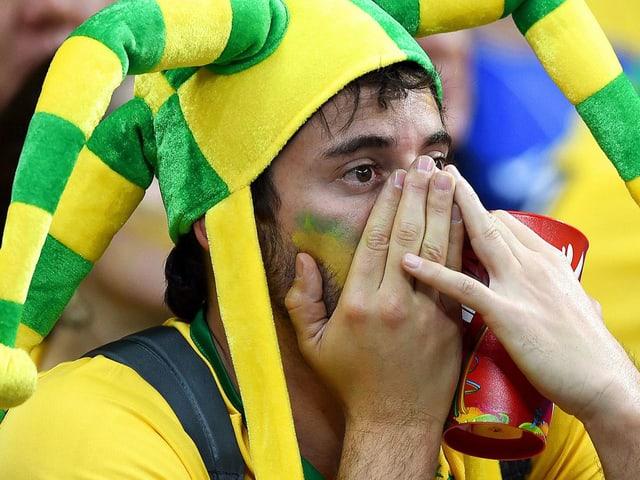 Brasilien-Fan mit Händen vor den Augen.