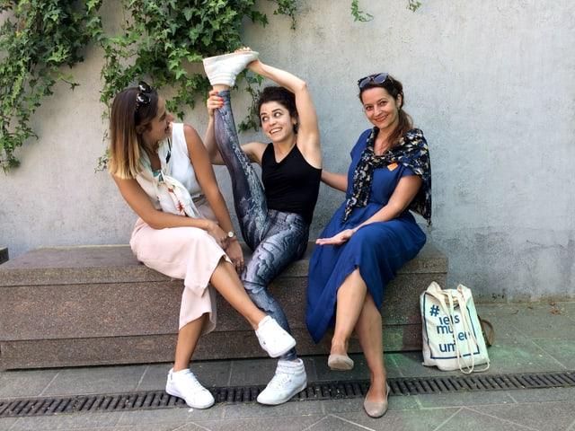 Drei Frauen sitzen auf einer Bank, eine streckt das Bein in die Luft.