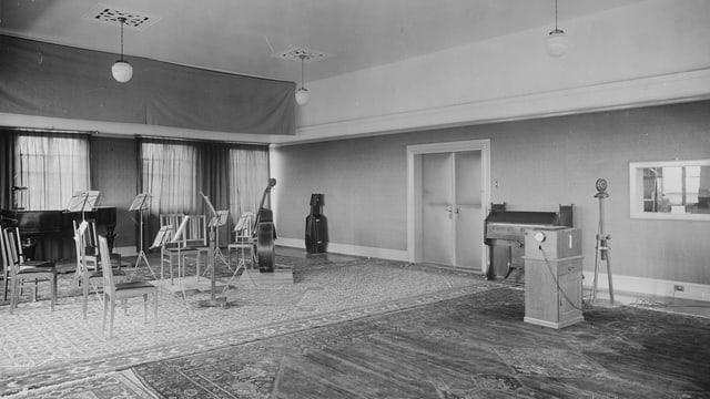Ein Zimmer mit Stühlen und Notenständern links und einem Klavier und Mikrofon rechts.