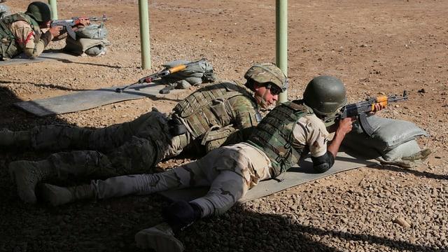 Zwei Soldaten in unterschiedlicher Kampfmontur liegen auf dem Boden, der eine zielt mit einem Gewehr, der andere schaut ihm dabei zu.