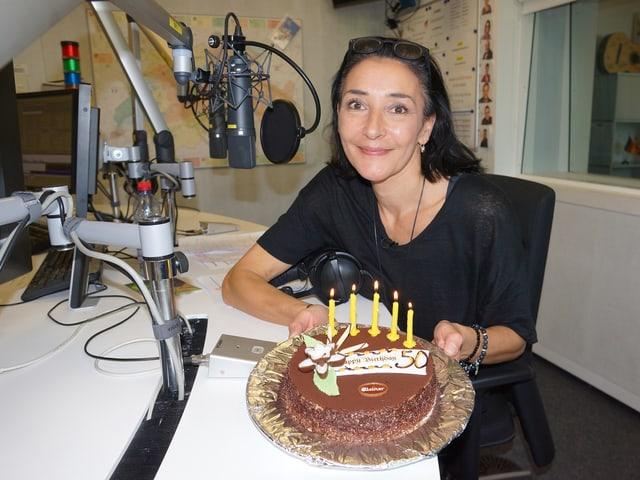 Eine dunkelhaarige Frau mit einer Geburtstagstorte in einem Radiostudio.