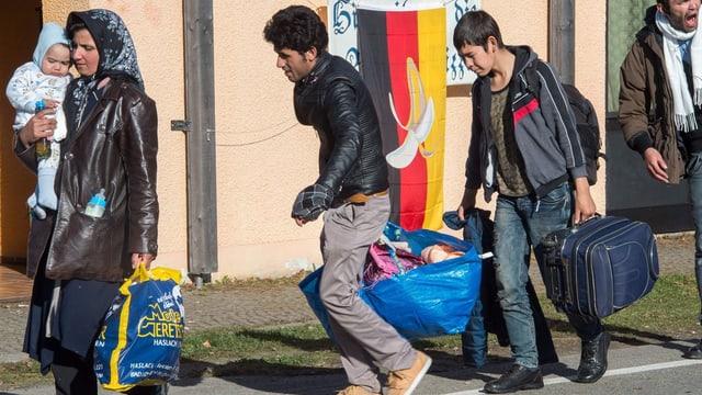 Flüchtlinge laufen an einer deutschen Flagge vorbei.