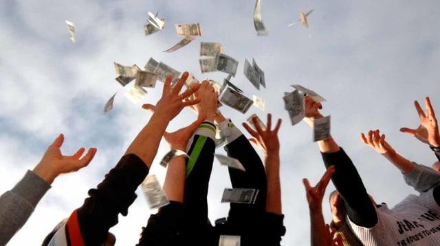 Ein paar Menschen werfen Geldscheine in die Luft.