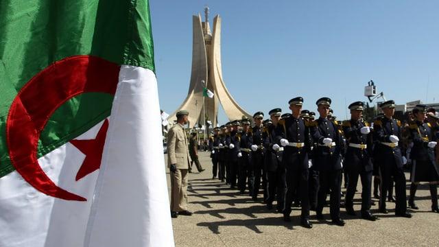 Militärparade mit algerischer Flagge im Vordergrund.