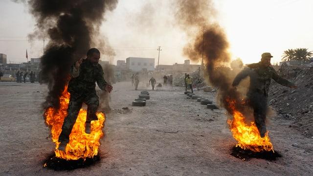 Zwei irakische Soldaten im Training rennen nebeneinander durch ein Feuer.