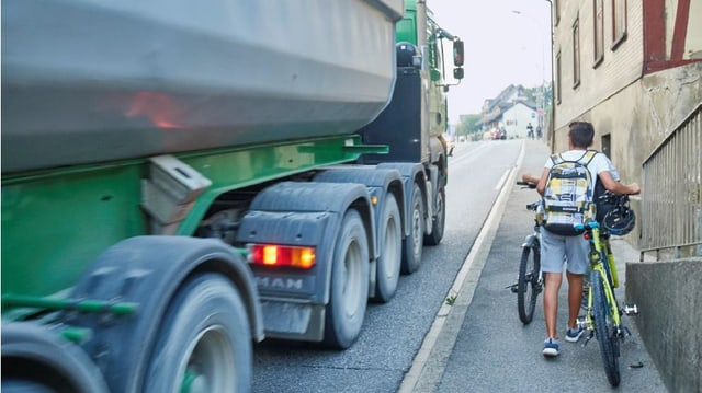 Velofahrer schieben ihr Velo auf einem schmalen Trottoir, auf der schmalen Strasse fährt ein Lastwagen vorbei.