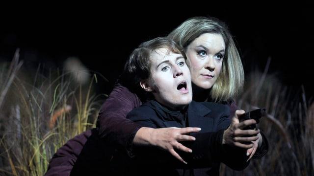 Zwei Frauen auf einer Bühne: Vorne Stéphany mit Kurzhaarschnitt, hält eine Pistole. Die andere Frau greift von hinten an ihre Arme.