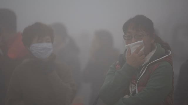 Zwei Chinesinnen mit Mundschutz im Smog