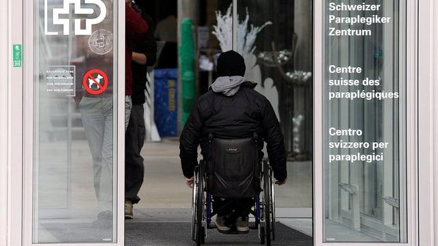 Eingang des Zentrums mit Rollstuhlfahrer von hinten.