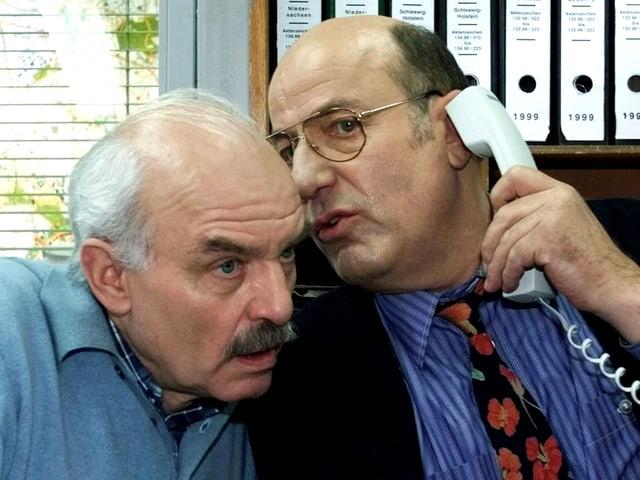 Die beiden Kommissare stecken die Köpfe zusammen, Manfred Krug (links) hat einen Telefonhörer in der Hand.