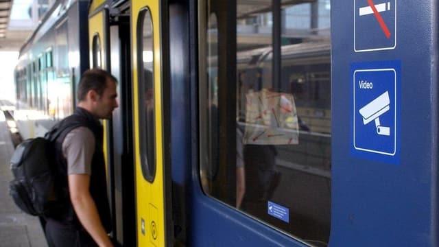 Ein Mann steigt in den Zug ein.