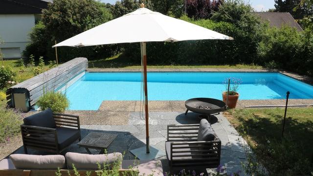 Ein Sonnenschirm an einem Gartenpool. Er gibt bei diesem Sonnenstand nur einem Sitzplatz Schatten.