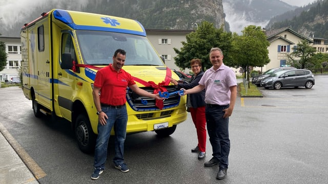 Reto Keller il directur dal spital Tusaun (da maun dretg) e Christine Demarmels surpiglian la clav dal nov vehichel ch'è vegnì construì a Volketswil/Turitg.