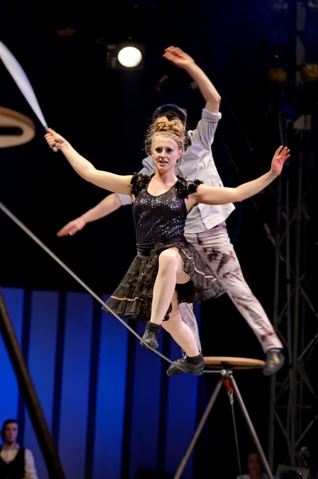 Frau auf einem Drahtseil in einer Zirkus-Manege.