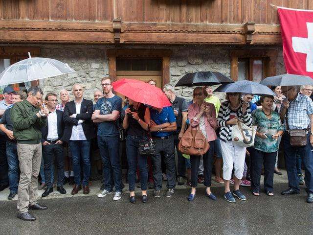 Das Publikum und einige Bundesräte suchen Schutz vor dem Regen